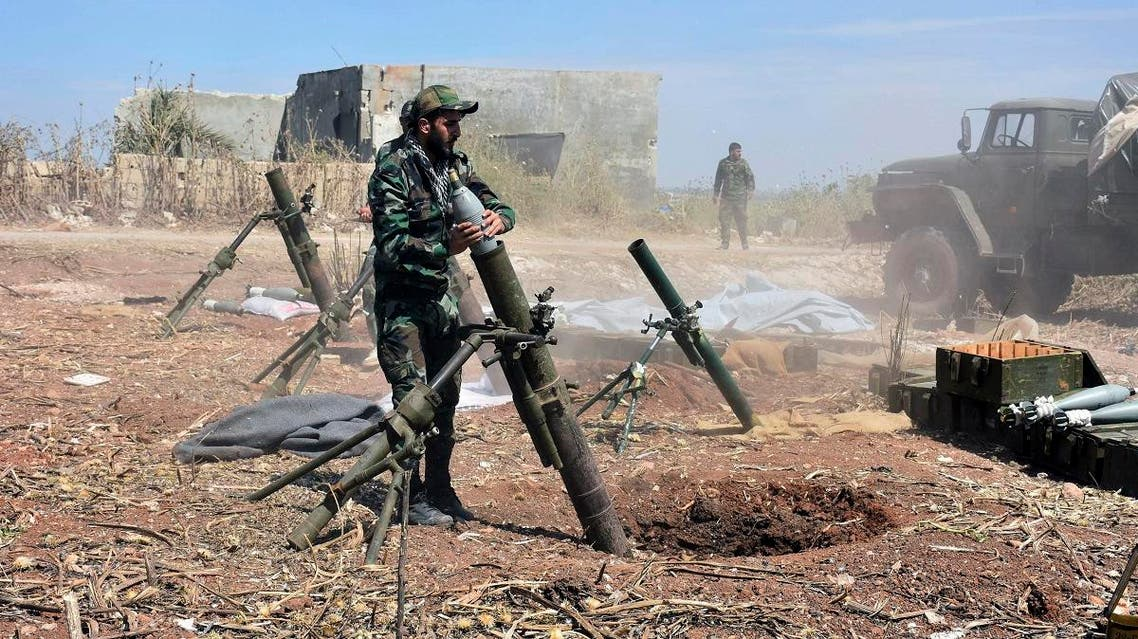 Syrian army soldiers prepare to launch a mortar towards insurgents in the village of Kfar Nabuda, in the countryside of Hama province. (AP)