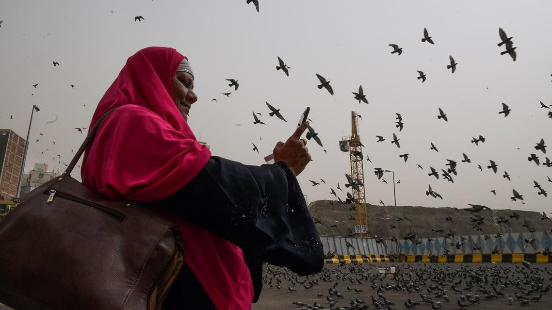 A Muslim pilgrim snaps pictures of pigeons as she walks in the streets of the Saudi holy city of Mecca. (AFP)