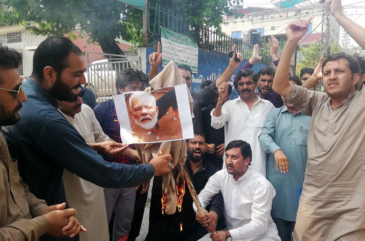 Pakistani Kashmiris burn a photograph of Indian Prime Minister Narendra Modi during an anti-Indian protest in Muzaffarabad, the capital of Pakistan-administered Kashmir. (AFP)