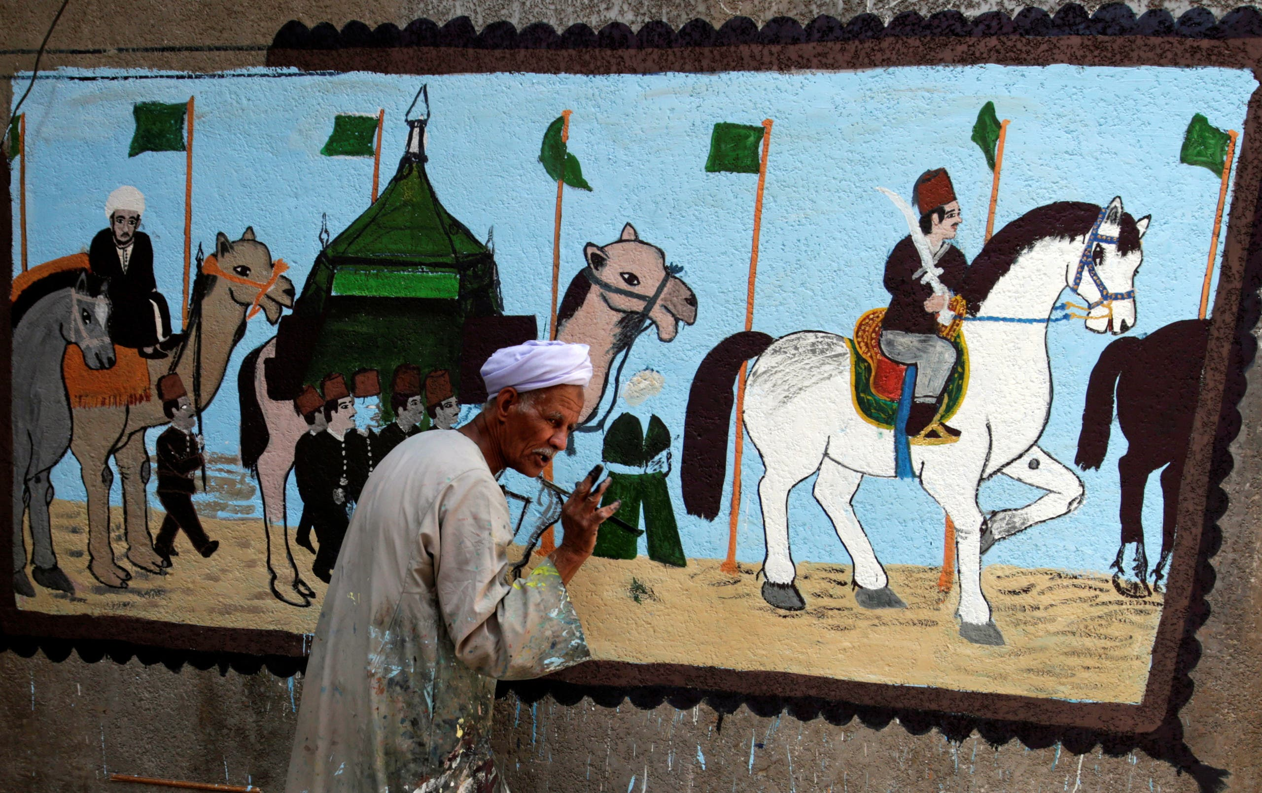 The artist Eid Al Salwaawi paints murals about the holy Kaaba and the rituals of the Hajj pilgrimage to Mecca, in Cairo. (Reuters)
