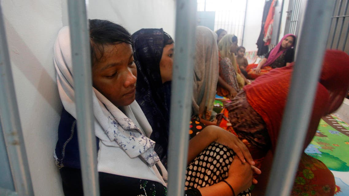 In this June 12, 2019, file photo, Rohingya refugees sit behind bars at a police station in Satun province, southern Thailand after Thai officials say they have discovered 65 ethnic Rohingya Muslim refugees who were shipwrecked and stranded in southern Thailand. (AP)