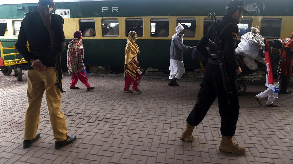 Pakistani policemen stand guard as stranded Indian passengers travelling with the Samjhauta Express, also called the Friendship Express that runs between New Delhi and Attari in India and Lahore in Pakistan, arrive at Lahore railway station on March 4, 2019. (AFP)