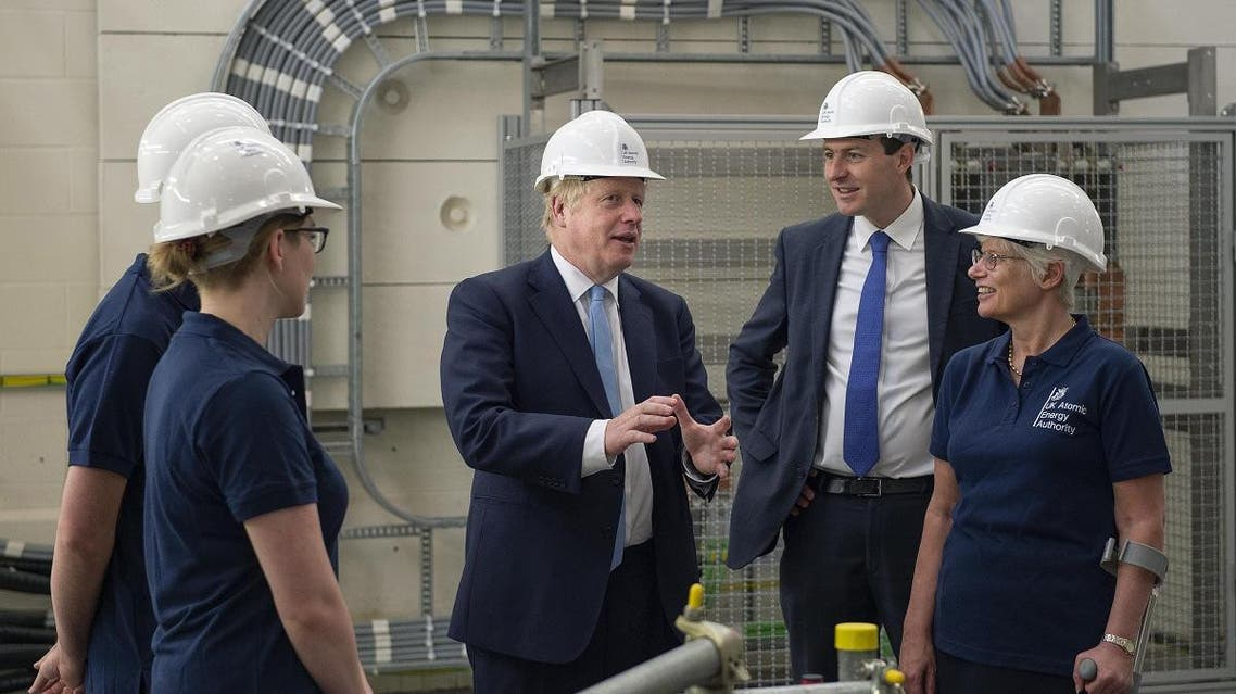 Britain's Prime Minister Boris Johnson (C) meets staff during his visit to the Fusion Energy Research Centre at the Fulham Science Centre in Oxfordshire, south east England on August 8, 2019. (AP)