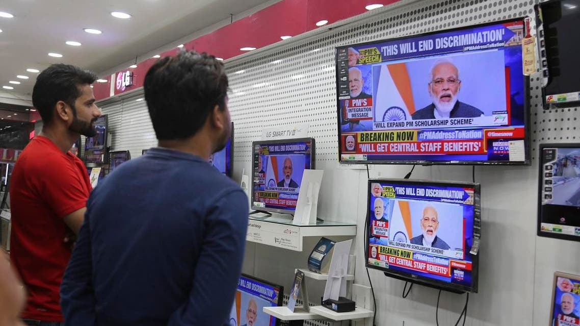 Indians watch Prime Minister Narendra Modi address the nation in a televised speech, in an electronics store in Jammu, India, Thursday, Aug. 8, 2019. (AP)