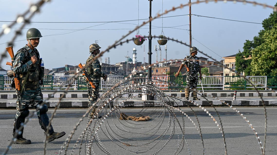 In this photo taken on August 5, 2019, Indian paramilitary troopers stand guard near a barbed fence wire as they block a road during a curfew in Srinagar. (AFP)
