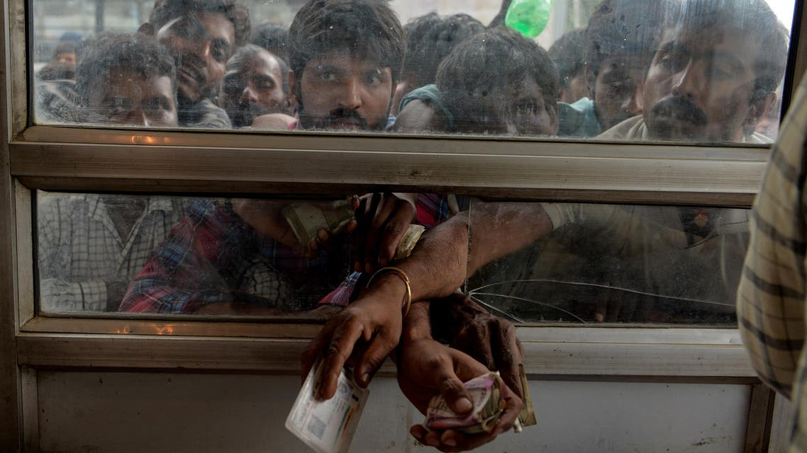 Labourers from across India working in Kashmir buy bus tickets at a counter of Jammu and Kashmir Tourist Reception Centre (JKTRC) to leave the city due to the heightened security situation in Srinagar on August 7, 2019. (AFP)