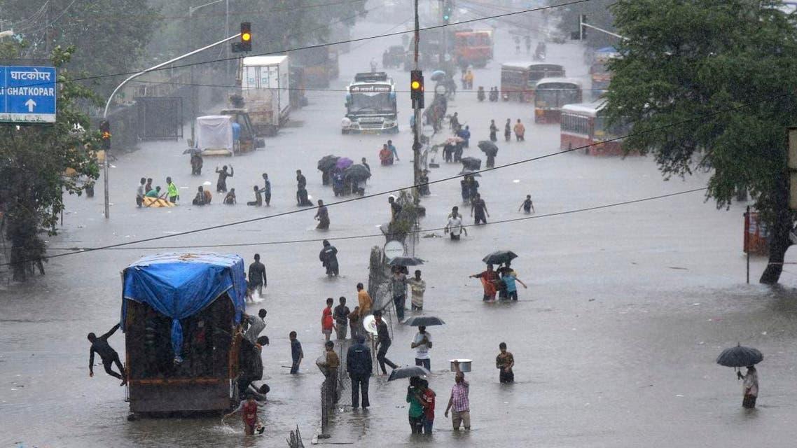 People walk through a flooded street following heavy monsoon rains in Mumbai, India. India's monsoon season runs from June to September. (AP)