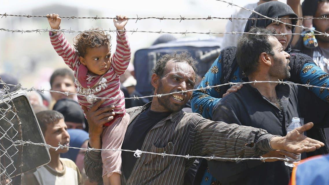 لاجئ سوري ينتظر وراء الأسوار الحدودية للعبور إلى تركيا