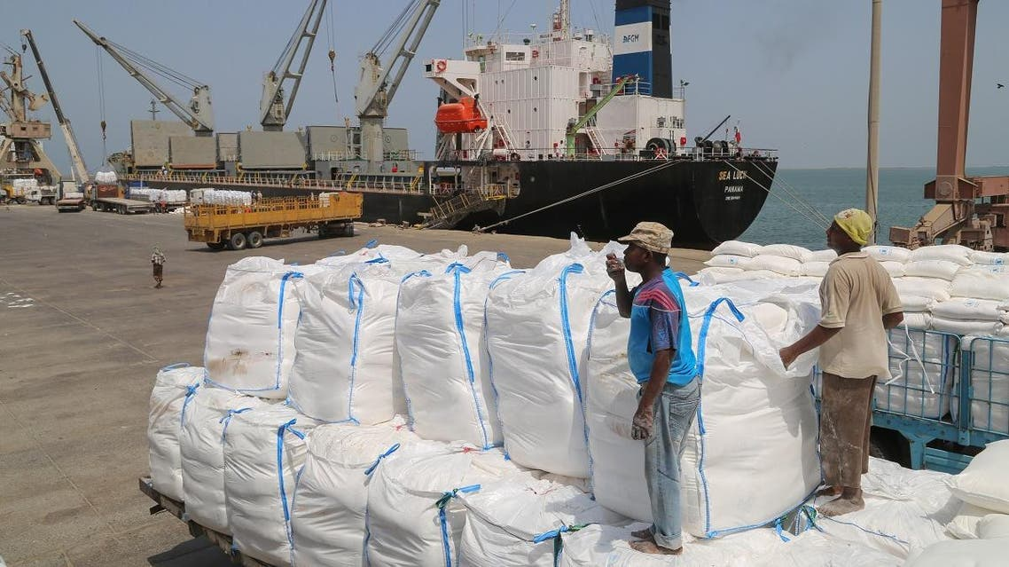 Yemenis receive sacks of food aid packages from the World Food Programme (WFP) in the Yemeni port city of Hodeida on June 25, 2019. (AFP)
