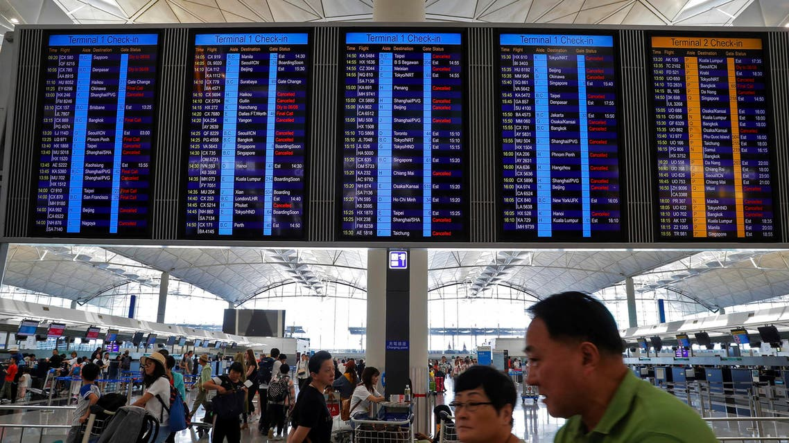 Traveller walk beneath an electronic billboard showing some flight cancellation information at the departure hall of Hong Kong International Airport in Hong Kong (AP)