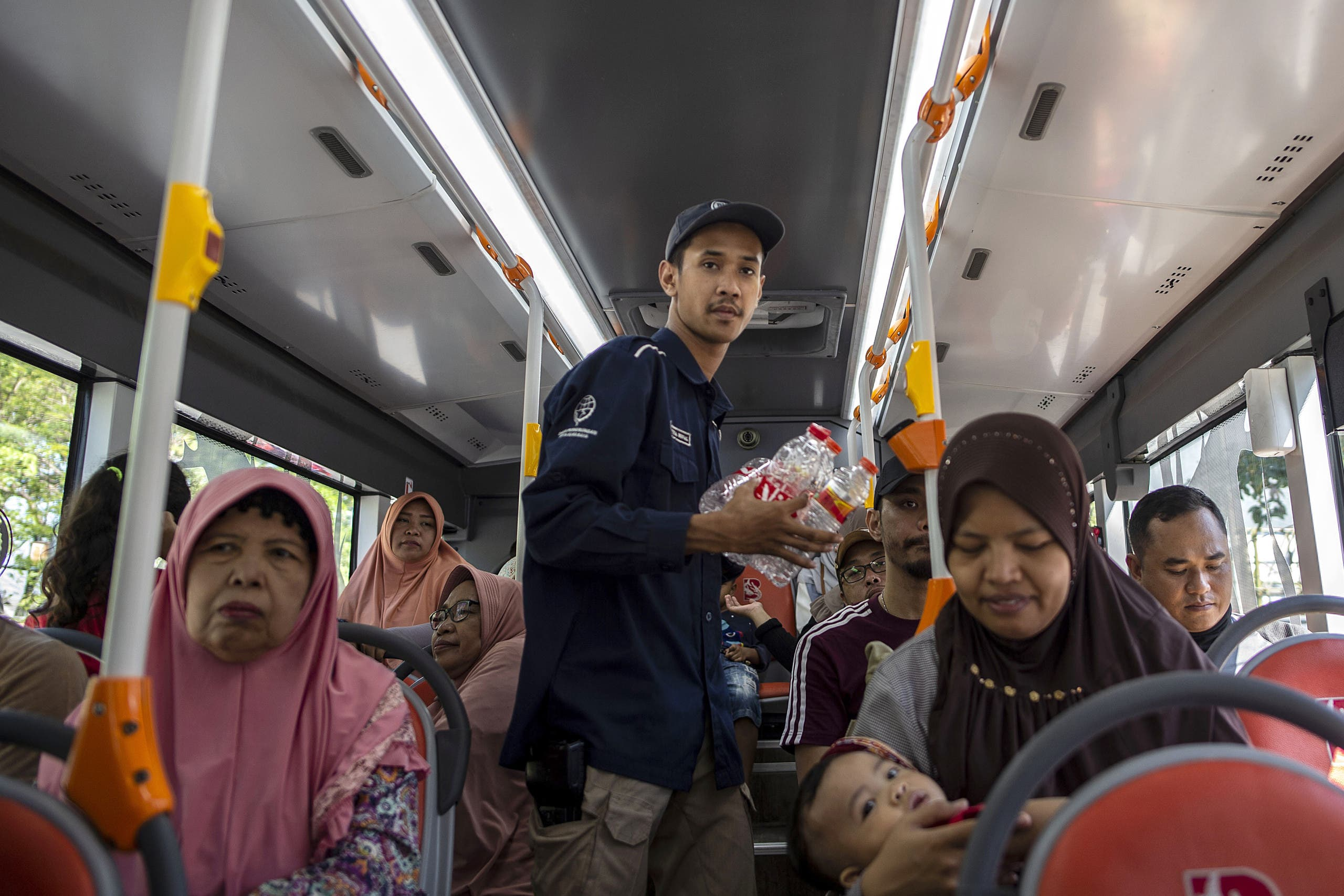 This picture shows a bus conductor collecting used plastic bottles as fare payment on board a Suroboyo bus in the Indonesian city of Surabaya. (AFP)