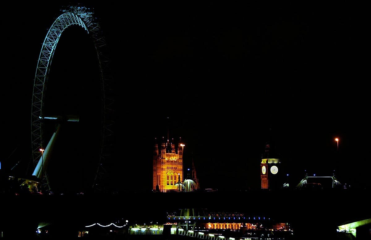 London landmark clock tower Big Ben (R) and the London Eye (L) are partly lit during a major power failure in the British capital London. (File photo: AFP)