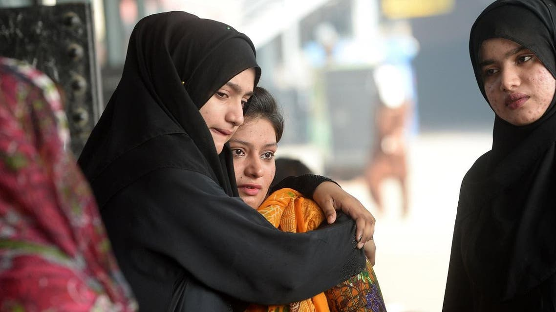 A Pakistani woman (L) embraces her Indian Muslim relative (C) ahead of her departure to India via the Samjhota Express train. (AFP)