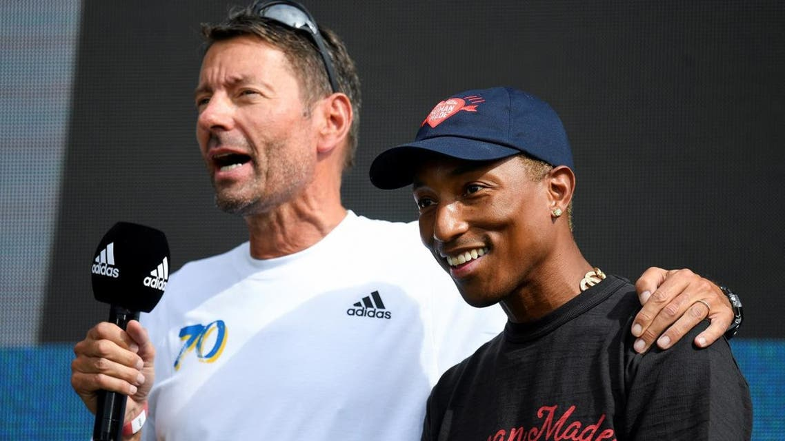 Adidas CEO Kasper Rorsted speaks next to singer Pharrell Williams as they attend the celebrations for Adidas' 70th anniversary at the company's headquarters in Herzogenaurach, Germany, on August 9, 2019. (Reuters)