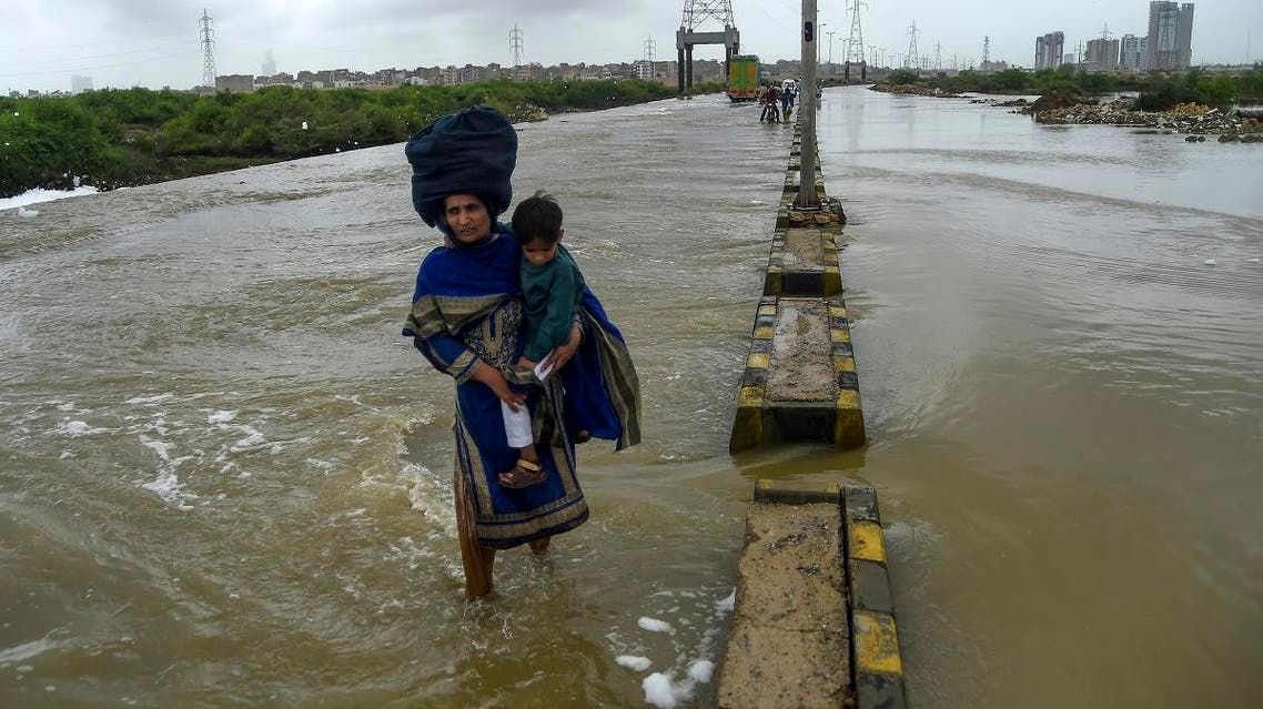 A woman holds her baby as she crosses a flooded street after heavy monsoon rains in Karachi on August 1, 2019. (AFP)