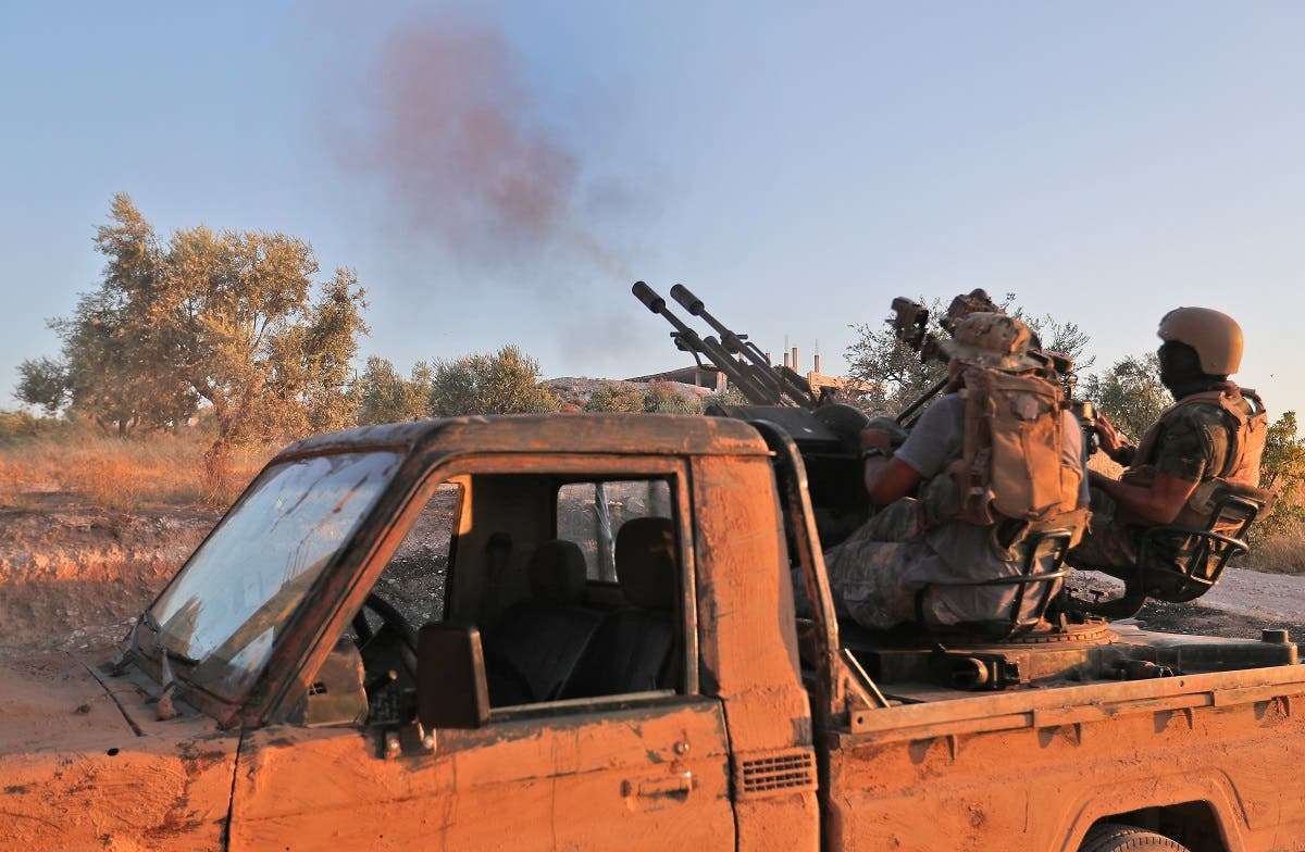 Fighters from the former al-Qaeda Syrian affiliate Hayat Tahrir al-Sham fire an anti-aircraft gun mounted on a pickup truck in Syria's southern Idlib province on August 7, 2019. (File photo: AFP)