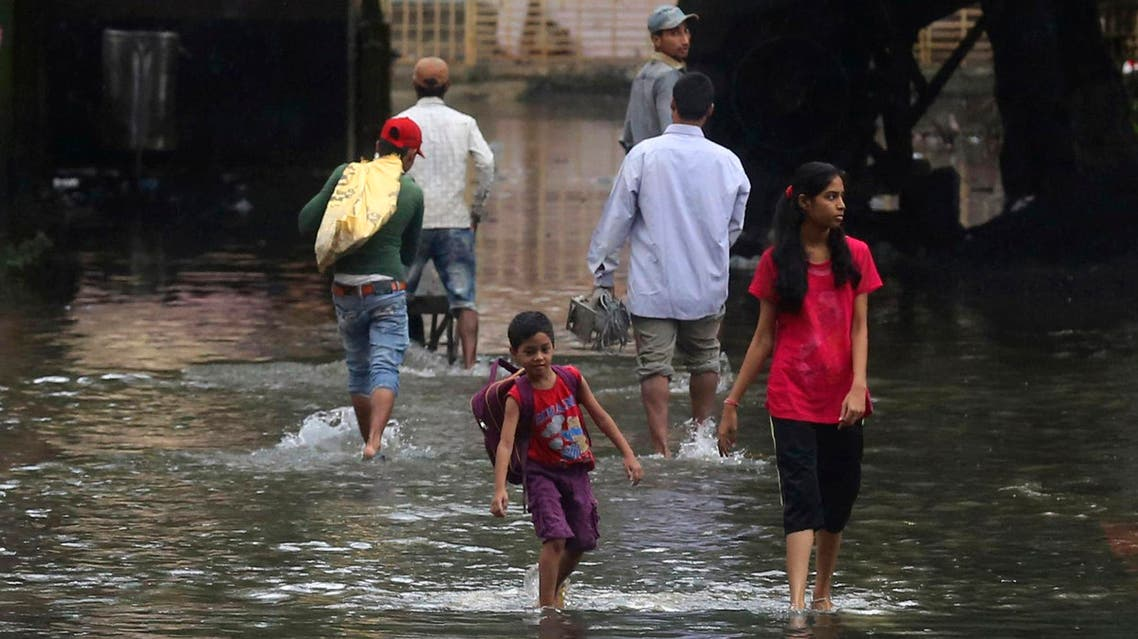 People walk past a waterlogged street after rainfall in Mumbai, India, Wednesday, July 24, 2019. (AP)
