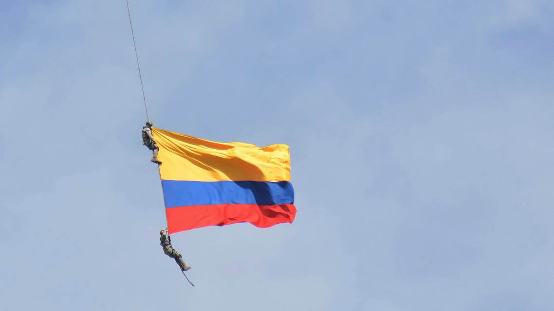 Two members of Colombia's air force have plunged to their deaths wrapped in their nation's flag when a cable hanging from a helicopter snapped while they were performing a mid-air stunt. (AP)