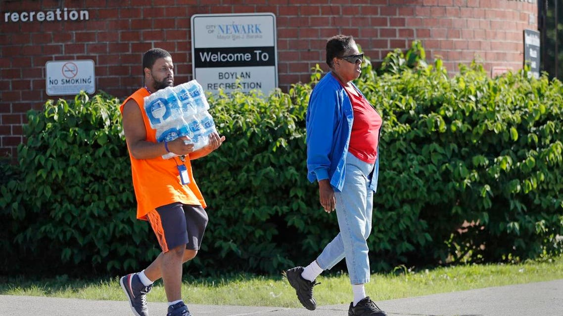 People leave the Boylan Street Recreation Center with cases of bottled water, Monday, Aug. 12, 2019, in Newark, N.J. (AP)