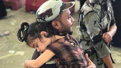 رجل أمن سعودي يحمل طفلة أثناء رمي أهلها للجمرات