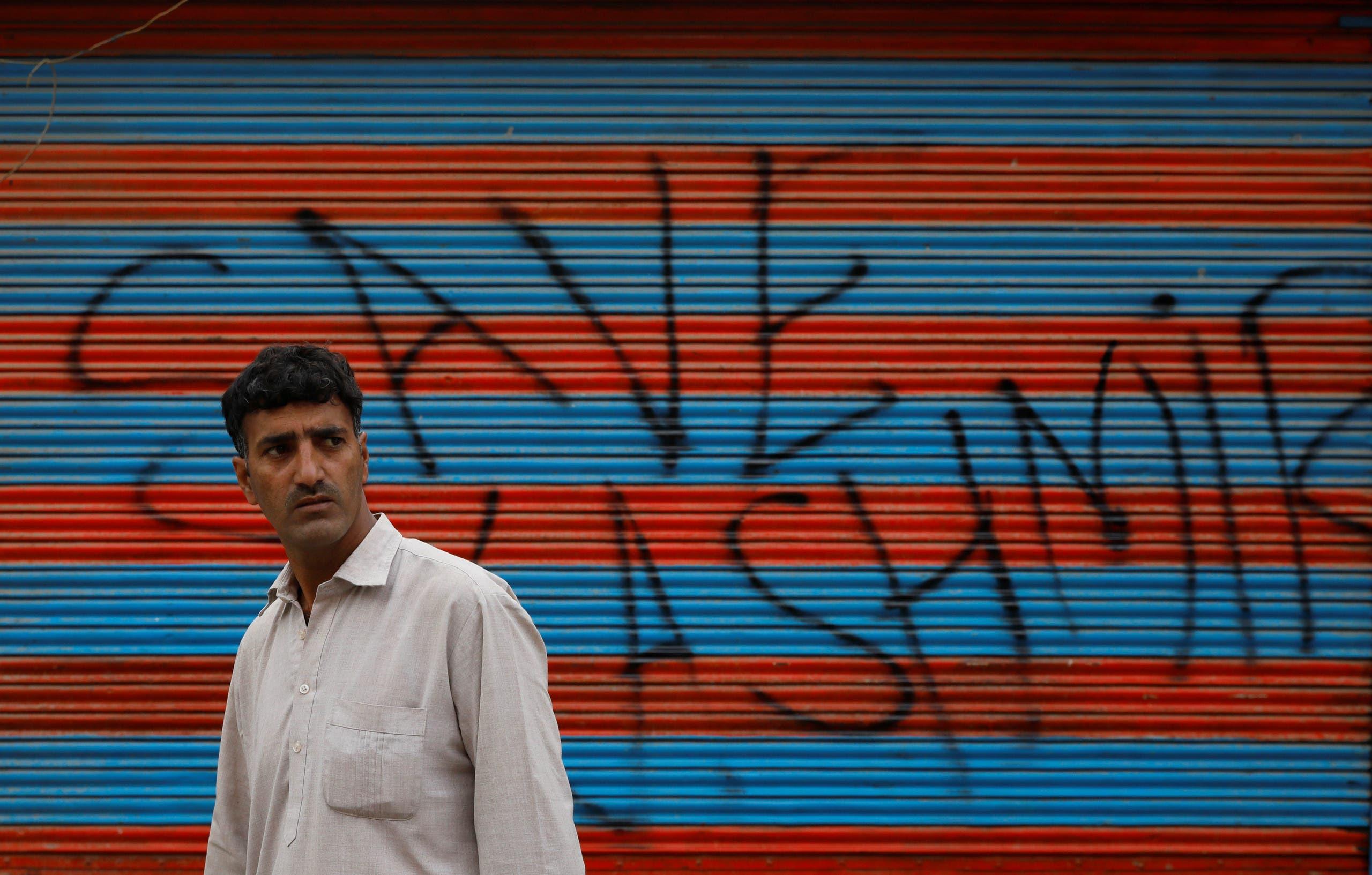 رجل يمر قرب متجر مغلق في كشمير كُتب على حائطه شعار مناهض للقيود الهندية