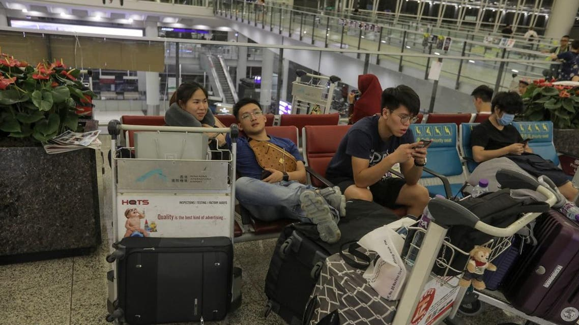 Stranded passengers sit near check-in counters as all flights have been cancelled after protesters occupied Hong Kong's international airport. (AFP)