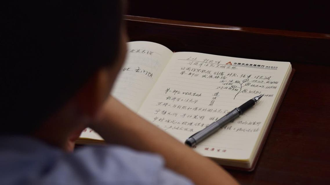This photo taken on June 26, 2019 shows an adult student taking notes on Xi Jinping thought in a class in a school in Beijing. (File photo: AFP)