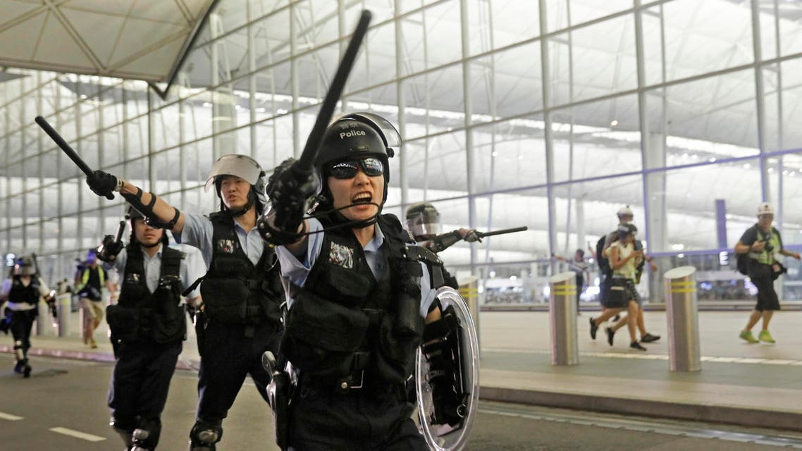 Policemen with batons and shields shout at protesters during a demonstration at the Airport in Hong Kong, Tuesday, Aug. 13, 2019.  (AP)