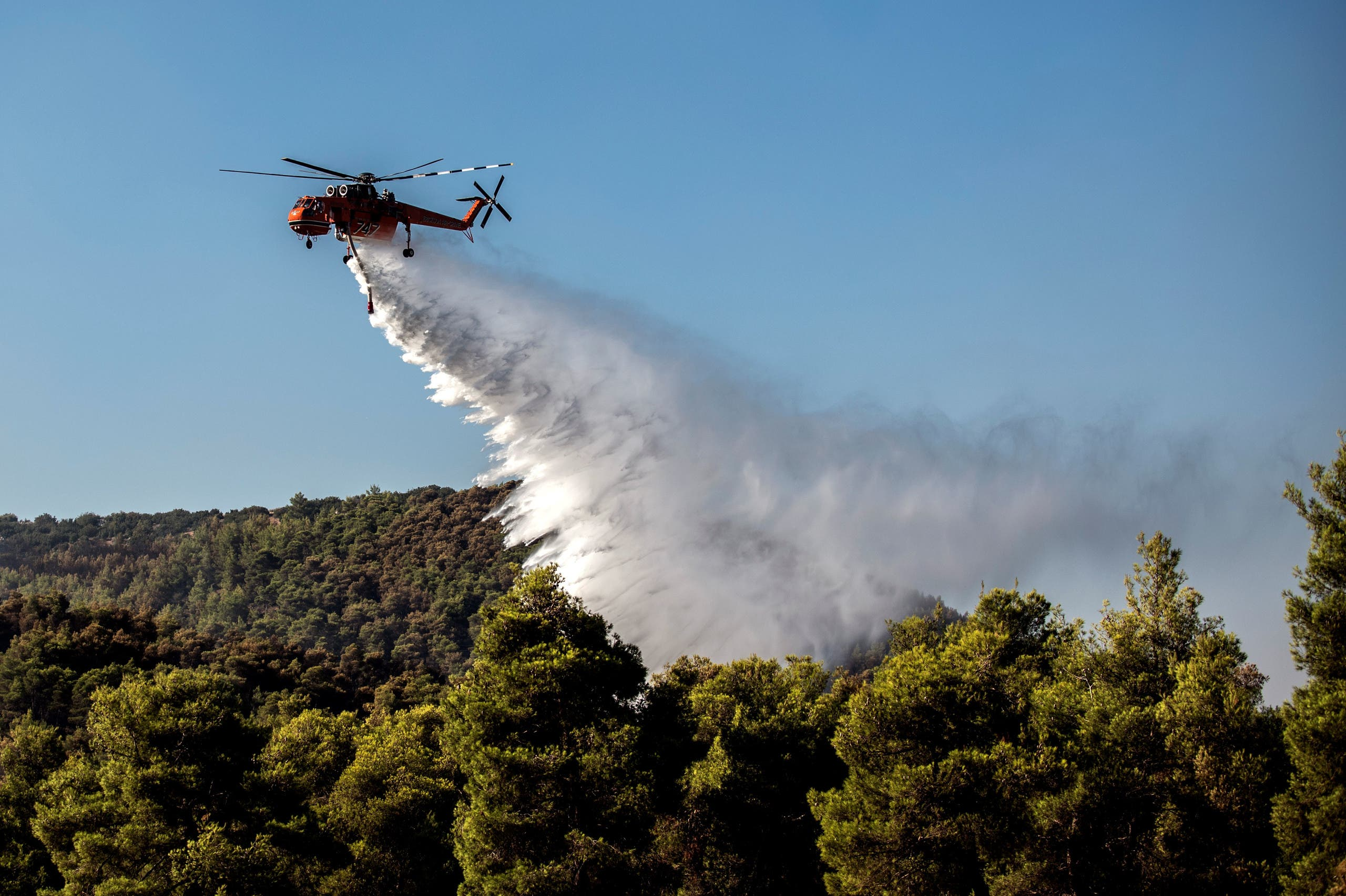 A firefighting helicopter drops water over a fire near the village of Makrimalli on the island of Evia, northeast of Athens. (AFP)