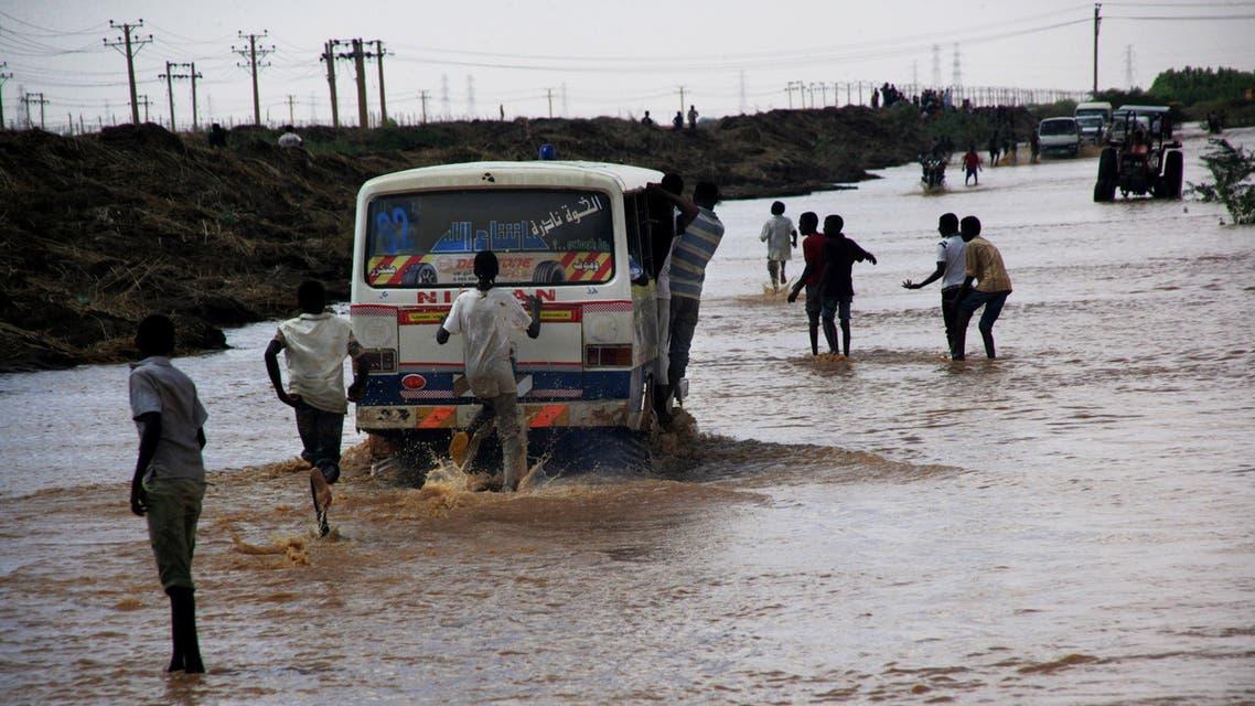 Sudanese men run in flood water to catch a bus in Khartoum, Sudan. (File photo: AP)