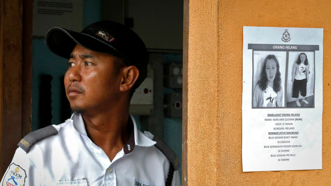 A security guard stands next to a notice showing a missing British girl in Seremban, Malaysia, Sunday, Aug. 11, 2019. (AP)