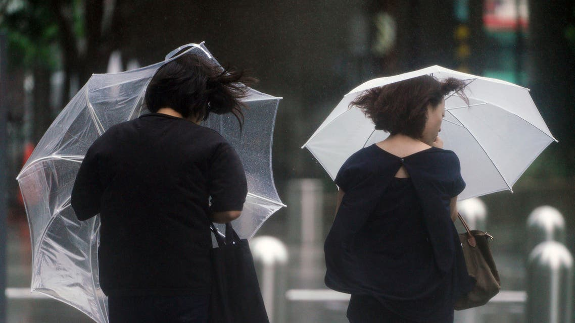 Women walk in the wind and rain as Typhoon Shanshan approaches Wednesday, Aug. 8, 2018, in Tokyo. (AP)