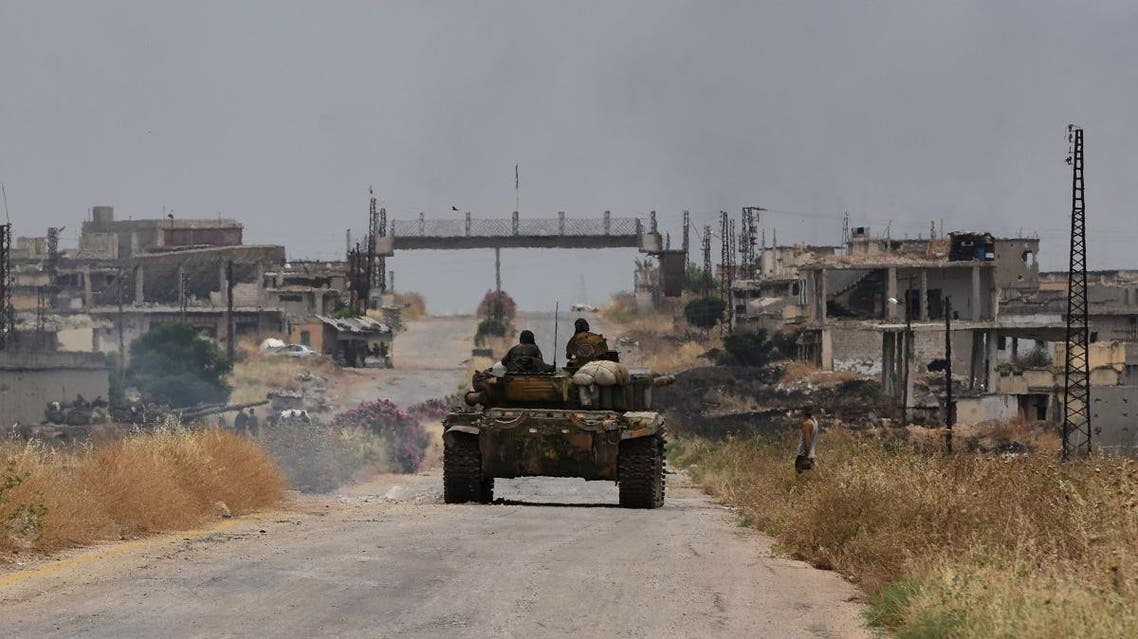 A tank belonging to the Syrian regime forces drives on a road in Hama. (AFP)