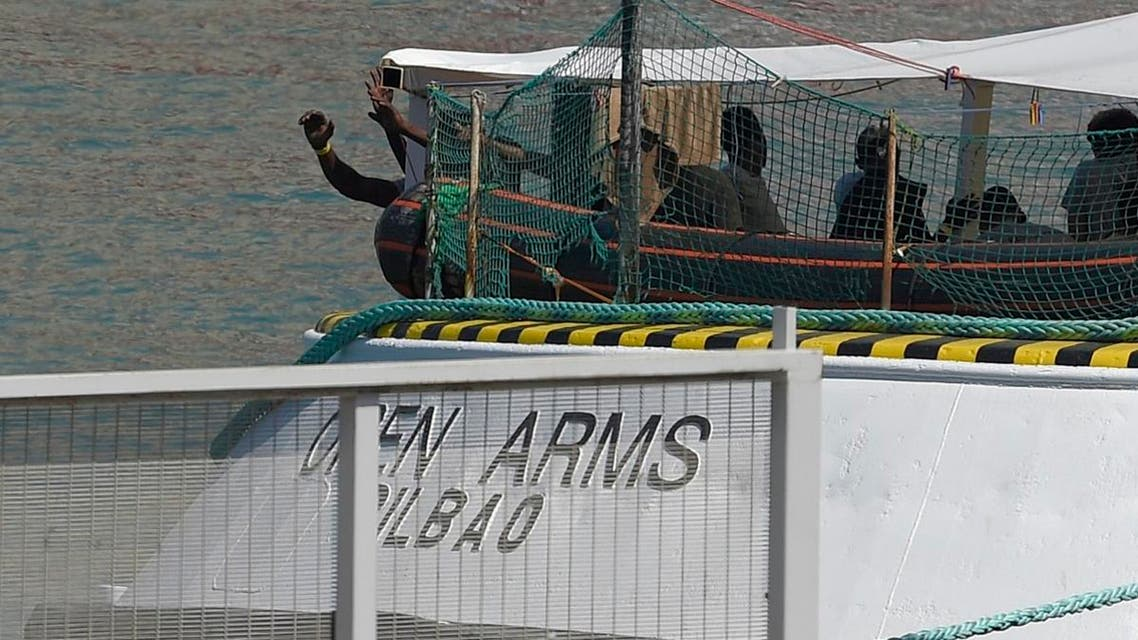 In this file photo taken on July 4, 2018 migrants stand on the deck of the Spanish NGO Proactiva Open Arms ship as it arrives at Barcelona's harbour, carrying 60 migrants rescued as they tried to cross the Mediterranean from Libya after Italy and Malta refused access. (AFP)