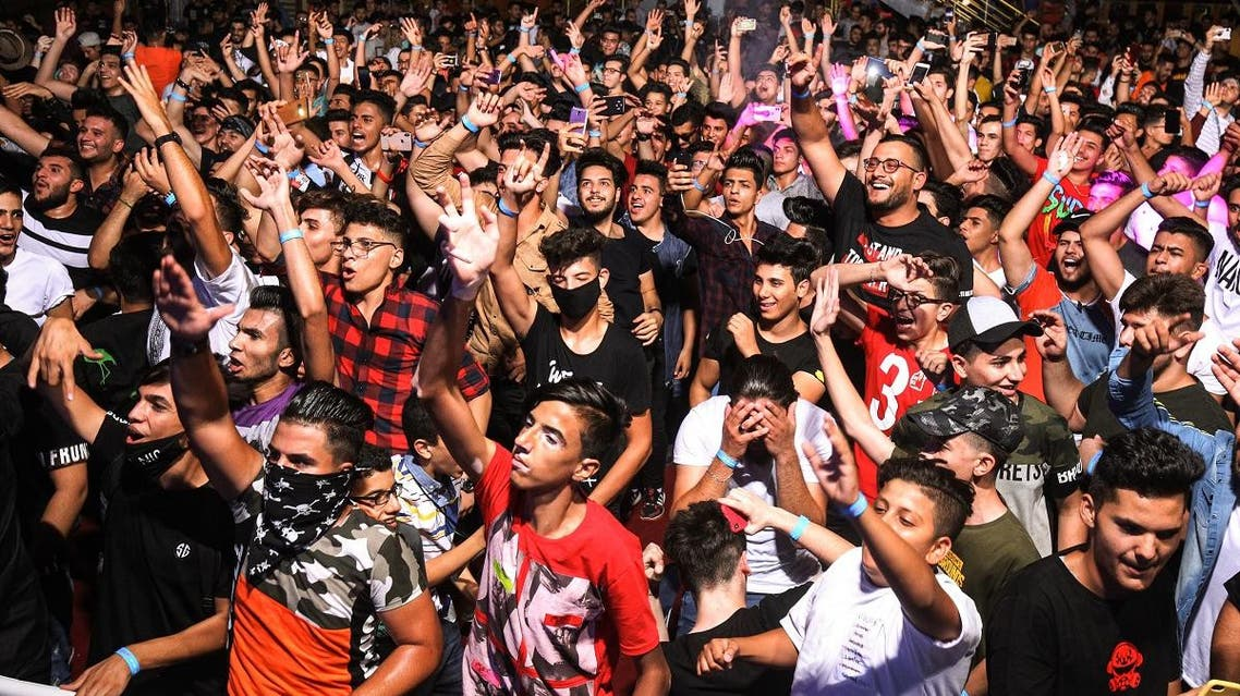 Youths attend an electronic dance music event, during the annual Baghdad Summer Festival at the People's Hall in the Iraqi capital on August 16, 2019. (AFP)