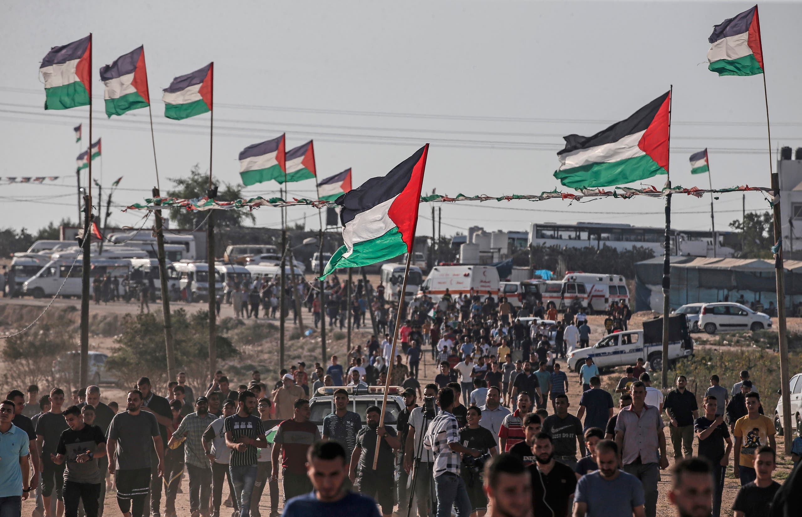 Palestinians demonstrate near the fence along the border with Israel in the eastern Gaza Strip on August 16, 2019.