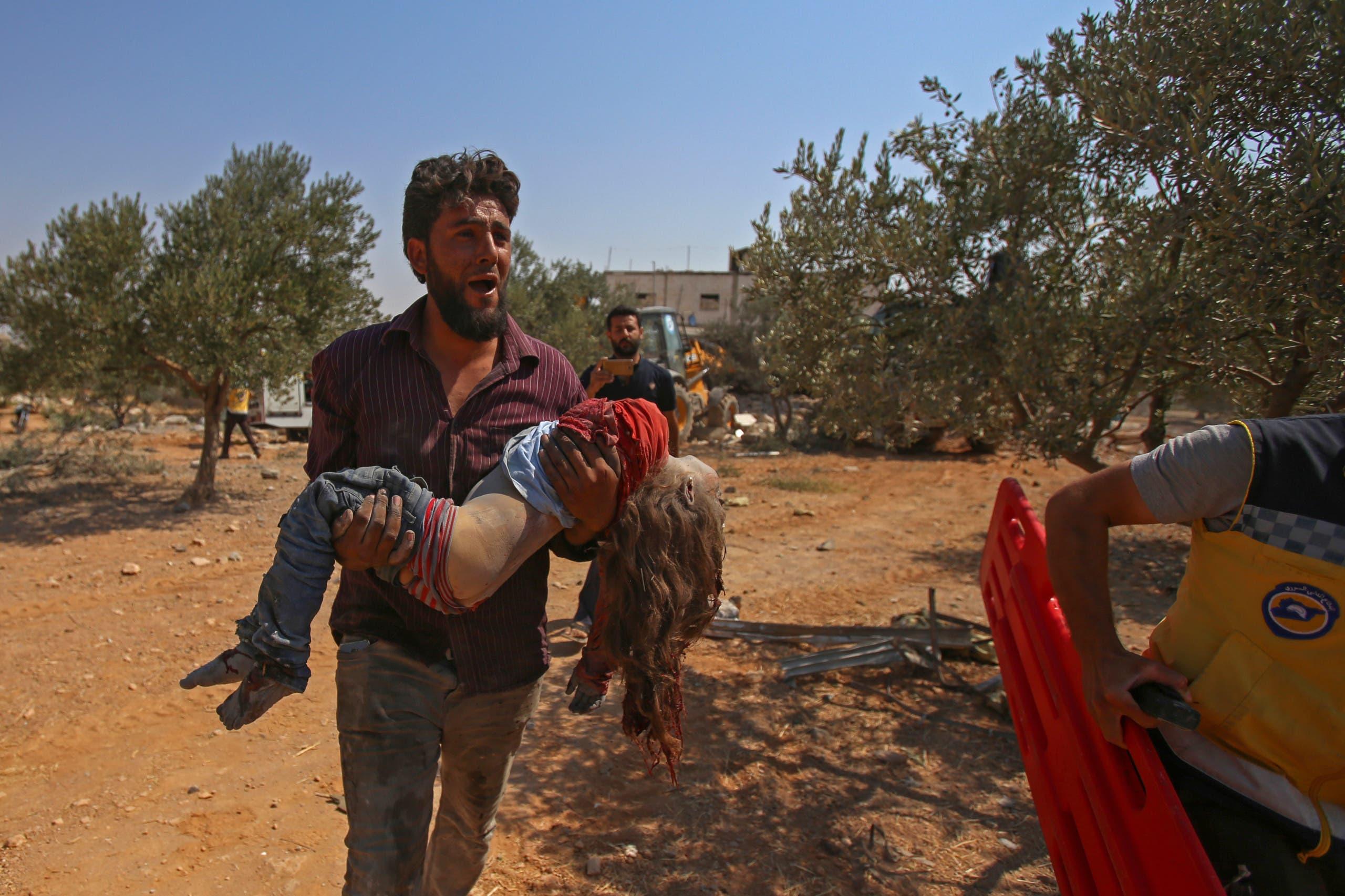 شاب يحمل جثة طفلة