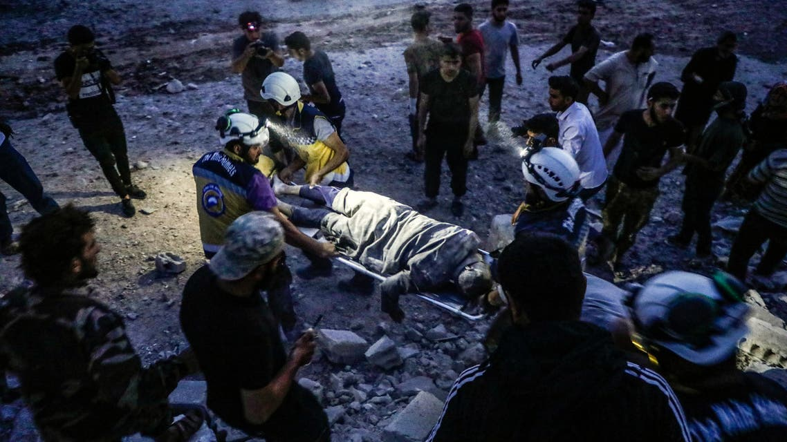 Members of the Syrian Civil Defence, also known as the White Helmets, carry away on a stretcher a man rescued from the rubble of a collapsed building following a reported air strike in Kfar Ruma in Syria's northwestern Idlib province, on August 16, 2019. Air strikes on August 16 by Syria's regime and its Russian ally killed 15 civilians in the area controlled by Syria's former Al-Qaeda affiliate Hayat Tahrir al-Sham (HTS) in Idlib province, said the Britain-based Syrian Observatory for Human Rights. The strikes came as regime forces battled HTS jihadists and allied rebels in the region, where fierce fighting claimed the lives of 13 loyalists and 18 jihadists and allied rebels, the Observatory said.
