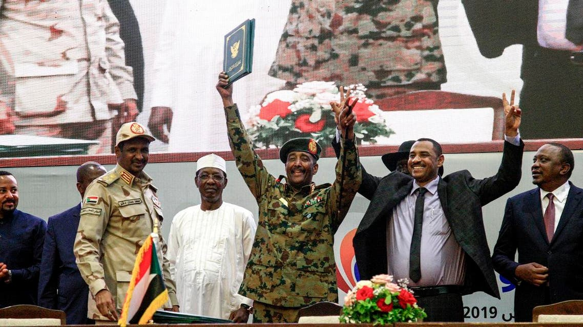 "Sudan's protest leader Ahmad Rabie (2nd-R), flashes the victory gesture alongside General Abdel Fattah al-Burhan (C), the chief of Sudan's ruling Transitional Military Council (TMC), during a ceremony where they signed a ""constitutional declaration"" that paves the way for a transition to civilian rule, in the capital Khartoum on August 17, 2019. (AFP)"