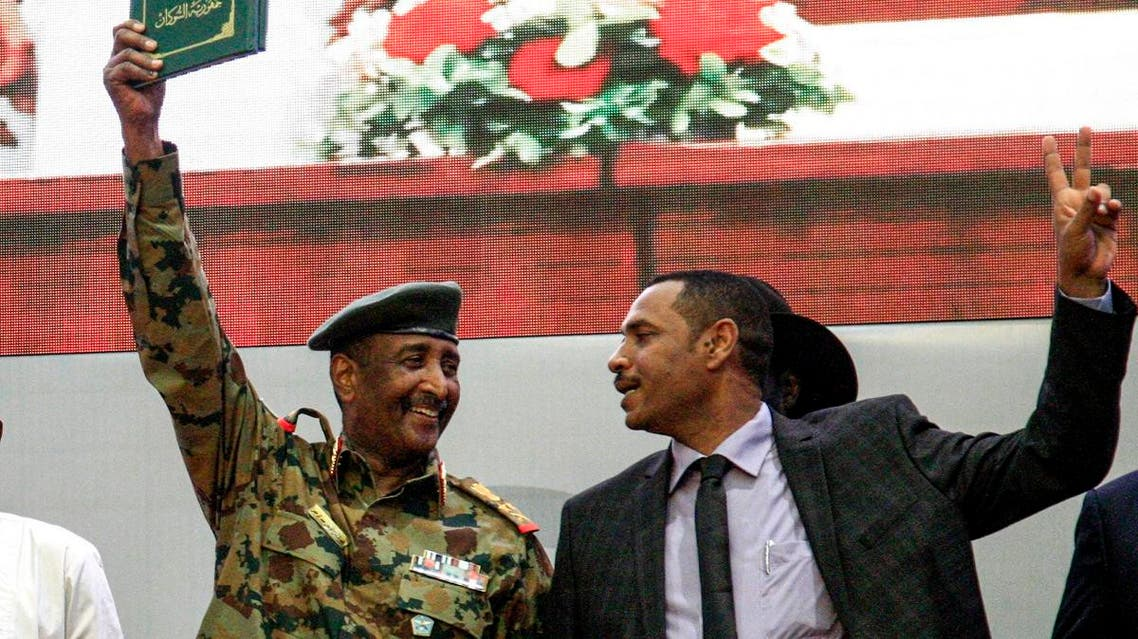 "Sudan's protest leader Ahmad Rabie (R), flashes the victory gesture alongside General Abdel Fattah al-Burhan (L), the chief of Sudan's ruling Transitional Military Council (TMC), during a ceremony where they signed a ""constitutional declaration."" (AFP)"