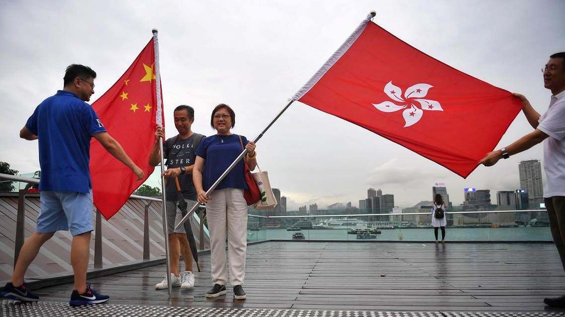 Pro-government supporters pose with the Hong Kong flag (R) and China national flag during a rally at Tamar Park in Hong Kong on August 17, 2019. (AFP)