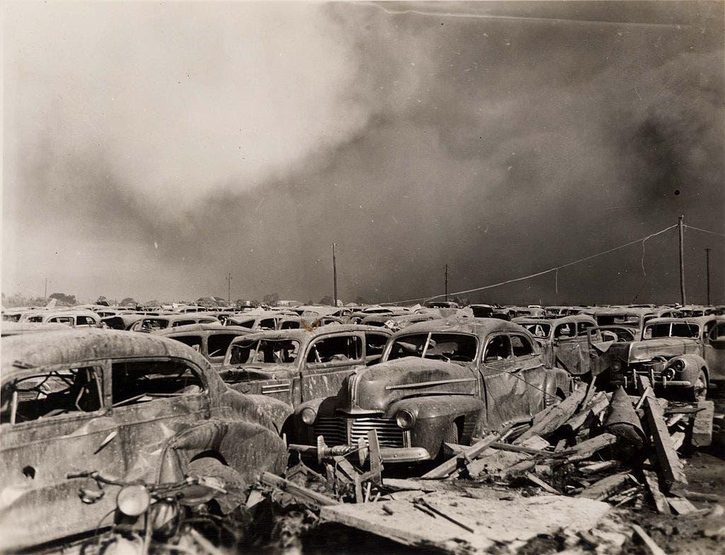 صورة تبرز عددا من السيارات المدمرة بموقف السيارات عقب الانفجار