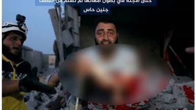 جنين يخرج من بطن أمه بعد تمزقه بقصف إدلب السورية!
