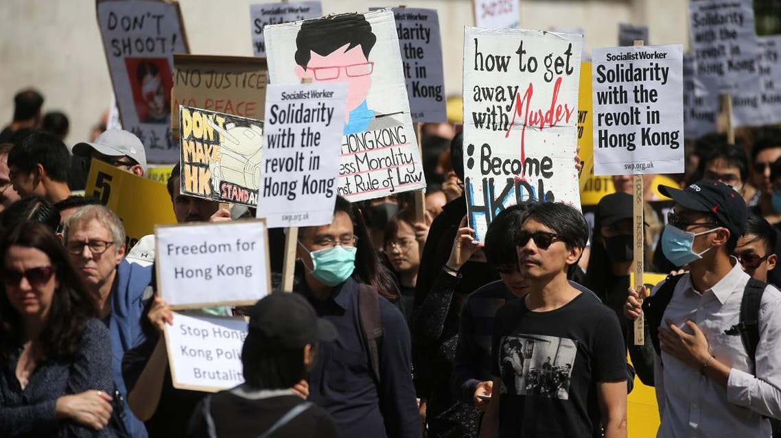 Protesters hold up placards as they gather in central London to attend a march organised by StandwithHK and D4HK in support of Pro-democracy protests in Hong Kong, on August 17, 2019. (AFP)