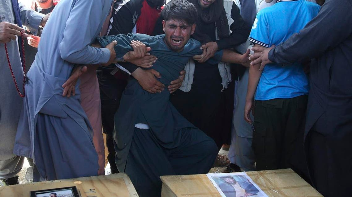 A relative wails near the coffins of victims of the Dubai City wedding hall bombing during a mass funeral in Kabul, Afghanistan, on  August 18, 2019. (AP)