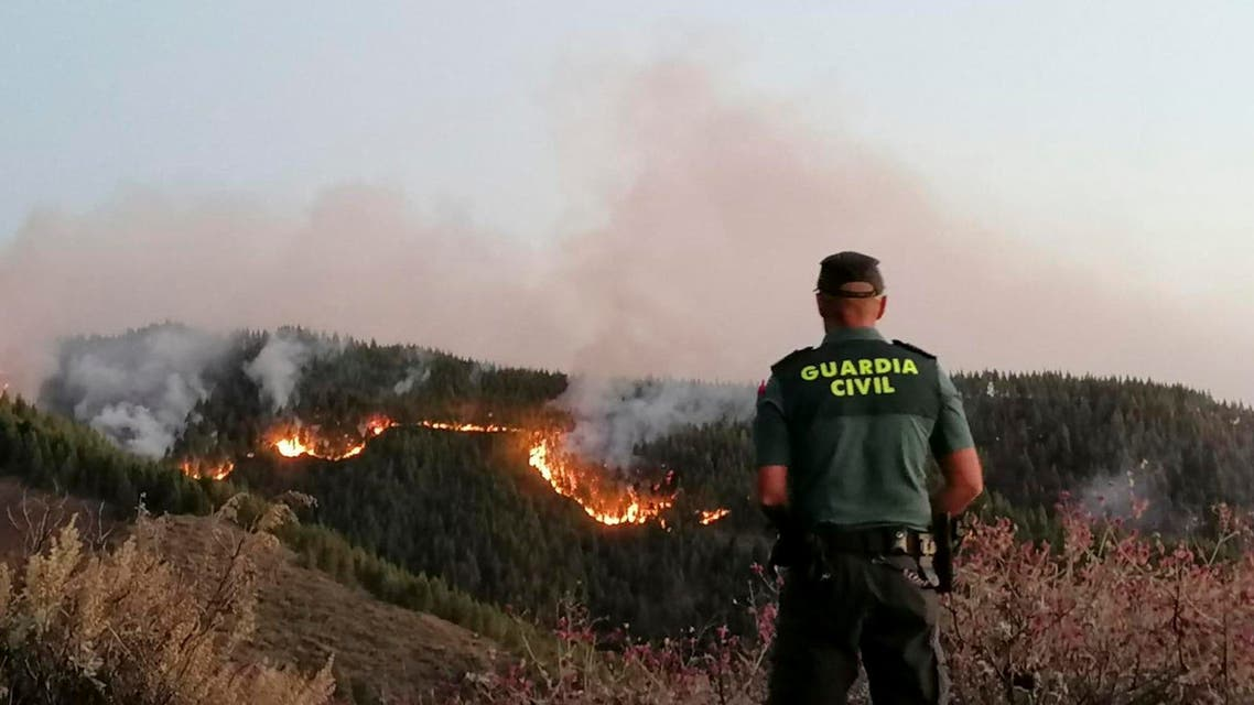 In this photo issued by the Guardia Civil, an officer looks at a forest fire in Gran Canaria, Spain, on Saturday Aug. 11, 2019. (AP)