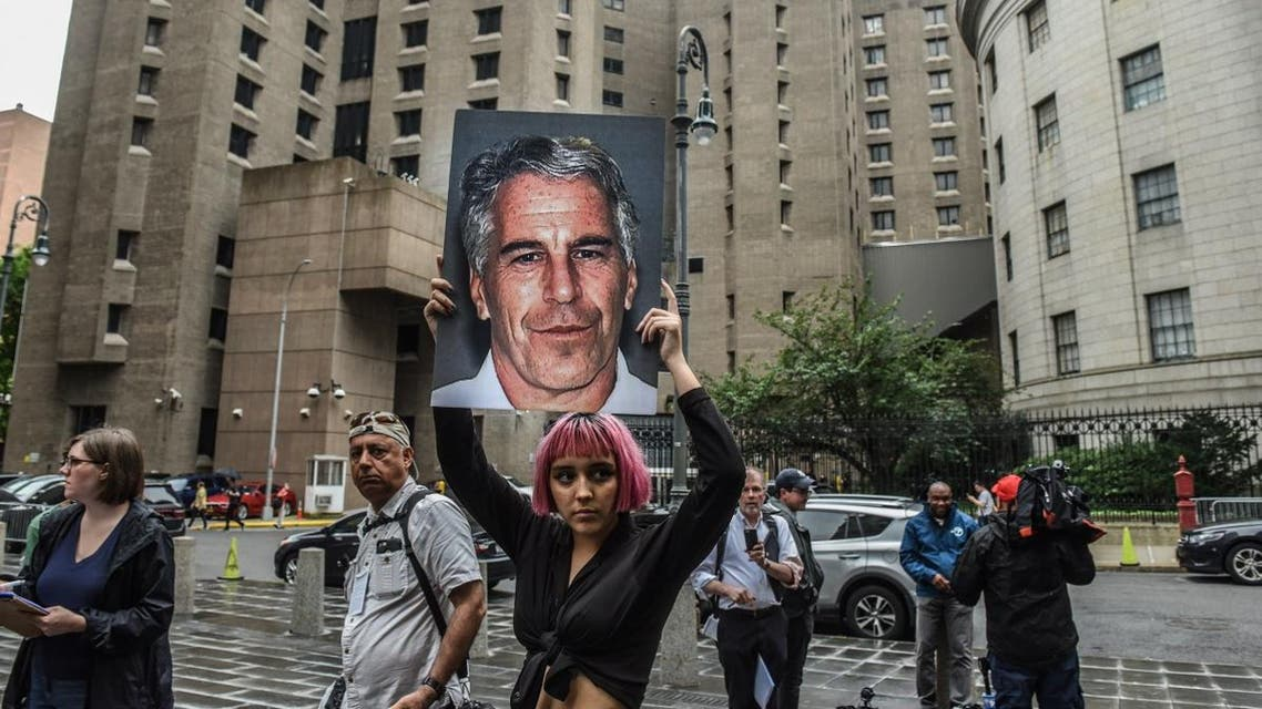 A member of a protest group holds up a sign of Jeffrey Epstein in front of the Metropolitan Correction Center on July 8, 2019 in New York City. (AFP)