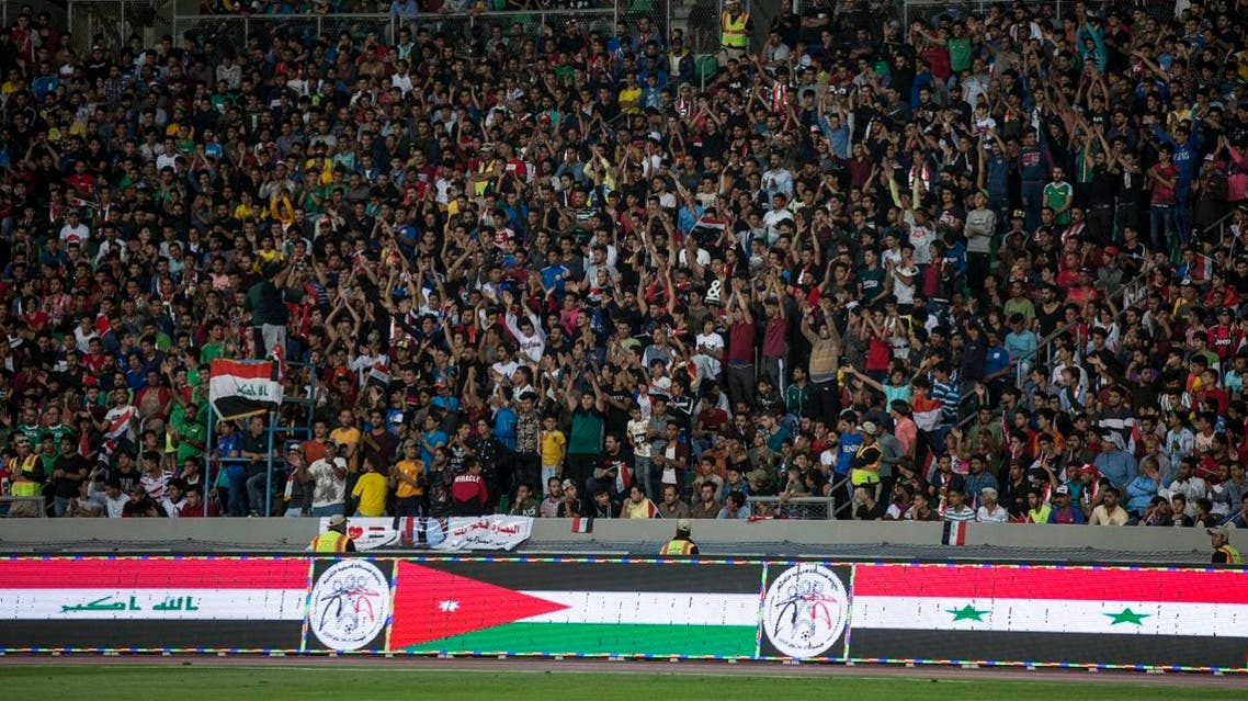 Iraqi football fans cheer as they watch the international friendly football match between Iraq and Syria at Basra Sports City Stadium on March 20, 2019. (AFP)