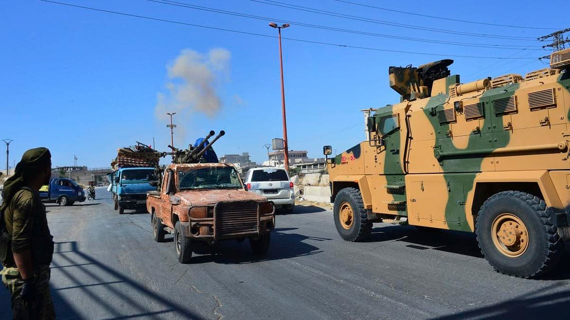 Smoke rises in the background from bombardment around the area as fighters with the Free Syrian army drive their pick-up truck, left, past a Turkish Armed Forces convoy. (AFP)