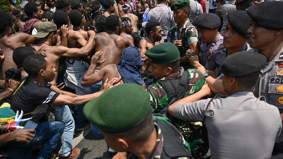 Papuan students taking part in a rally push toward a line of police and military blocking them in front of the army's headquarters in Jakarta on August 22, 2019. (AFP)